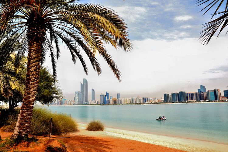 Skyline of Abu Dhabi from a sandy beach with palm trees
