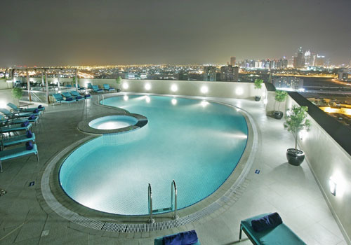 Night picture os a kidney shaped pool on a roof of a hotel with view over the city