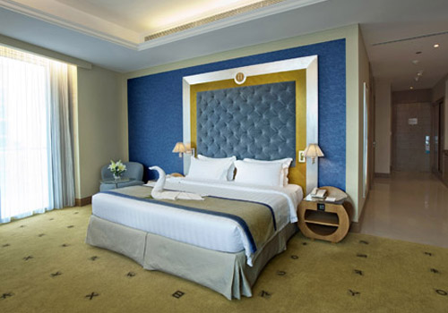 King bed in hotel with blue and gold decor and full wall windows