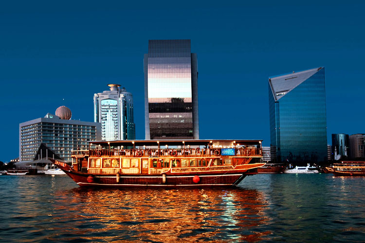 Luxury traditional wooden boat during sunset on the Creek of Dubai