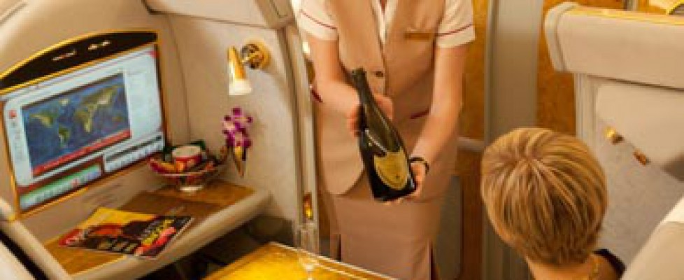 Flight attendant serving champagne on first class