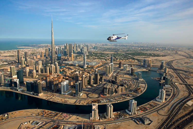 Helicopter flies above Dubai with Burj Khalifa in the background