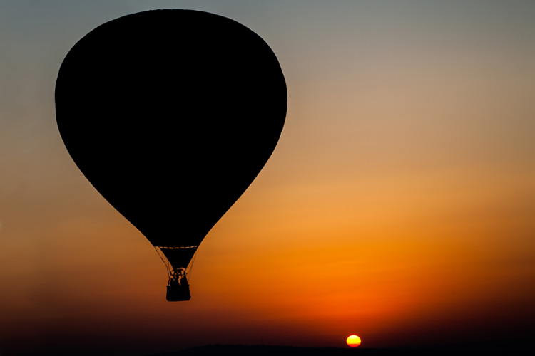 Hot Air Balloon flies above the desert with setting sun