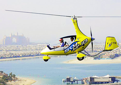 A yellow gyrocopter is flying above the sea in Dubai