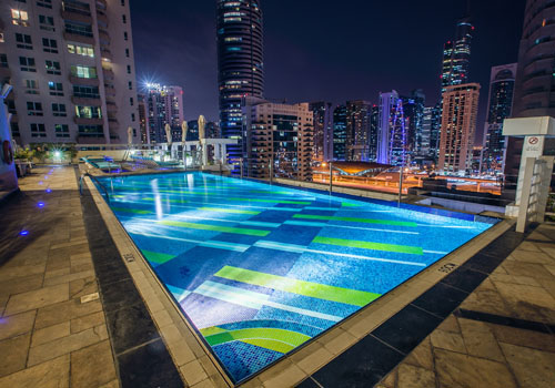Night image of a pool on the roof of a hotel with blue and green mosaic and city view