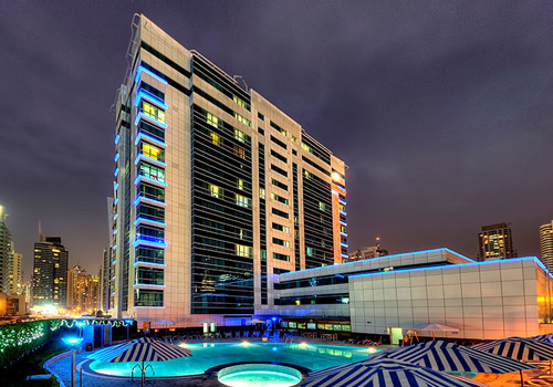 Night image of the pool area of a hotel with striped umbrellas