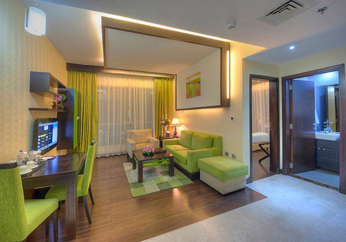 Living room in a hotel with bright green decor