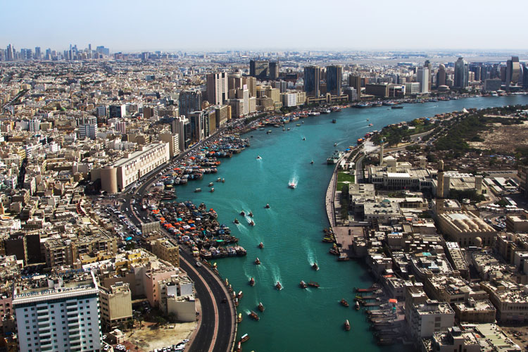 Aerial view of the Dubai creek with boats and the city behind