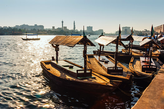 Old wooden boats on the creek of Dubai with old Dubai in the background