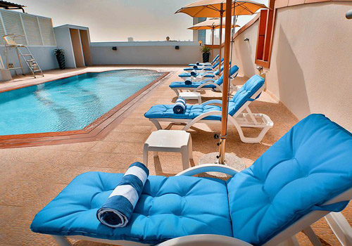 Pool area with blue sun beds on a hotel roof