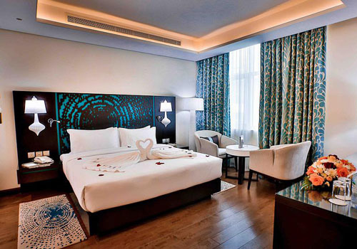 Hotel room with king bed and brown decor