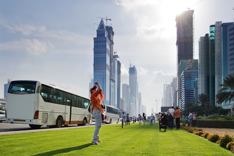 A woman is taking picture of tall buildings in front a tourist bus