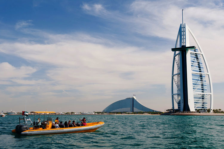 Ayellow boat with people n it is floating in front of Burj Al Arab