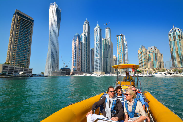 People are riding a yellow boat in the Dubai Marina