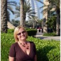 A woman is standing and smiling with palm trees in background