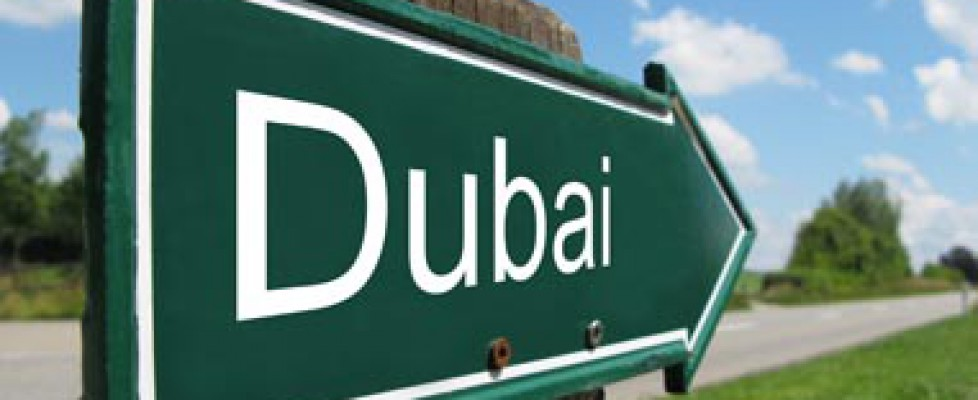 Green road sign pointing towards Dubai