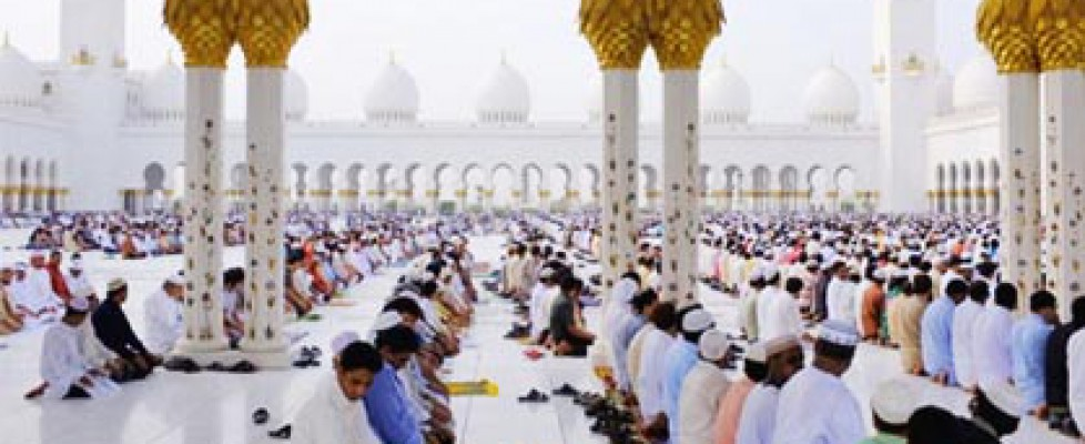 Men kneeling in rows praying in the white floors of Sheikh Zayed Mosque