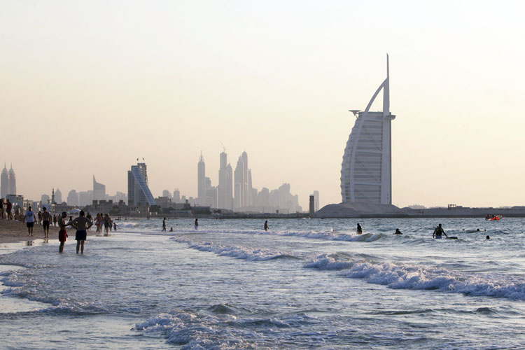 People are bathing in the sea with Burj Al Arab in the background