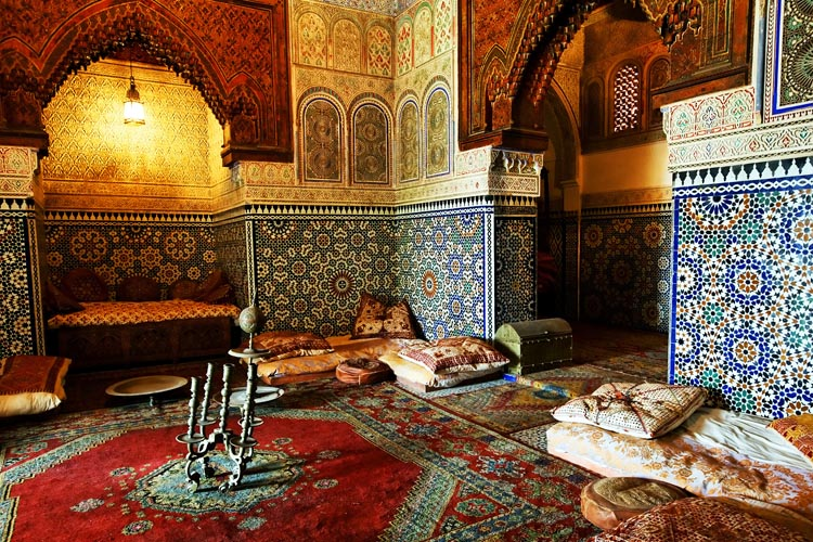 Inside of Middle Eastern room, with mosaic on walls, carpets and pillows