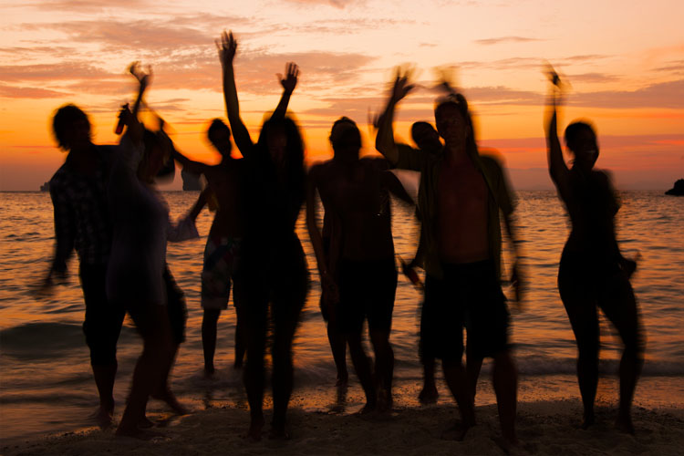 Young men and women are dancing on the beach in setting sun