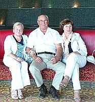 A man and two women are sitting in a hotel lobby